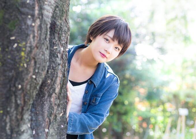 木から顔を出している女性