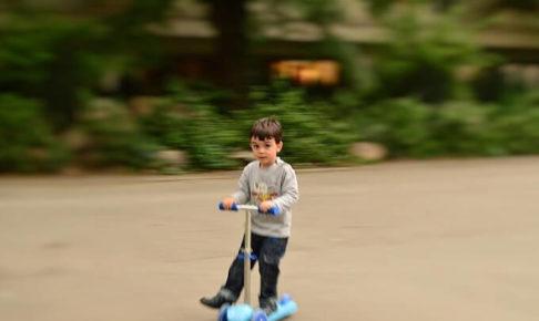 キックボードに乗っている少年