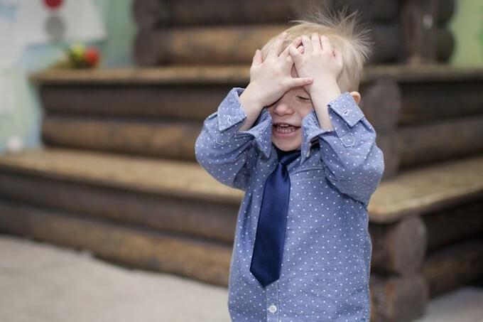 顔を覆っている子供
