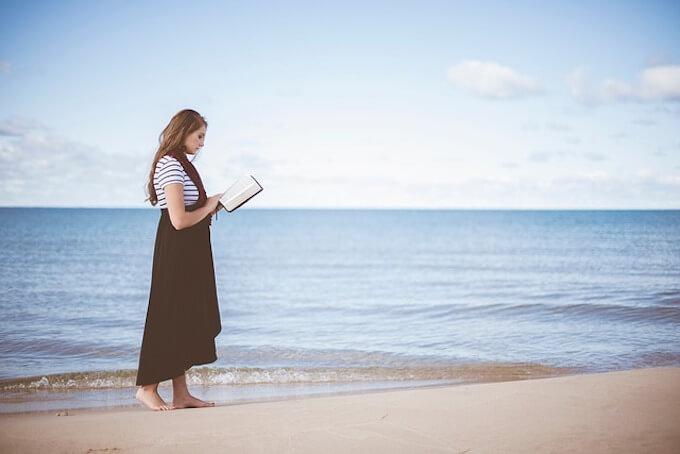 海辺で読書をしている女性